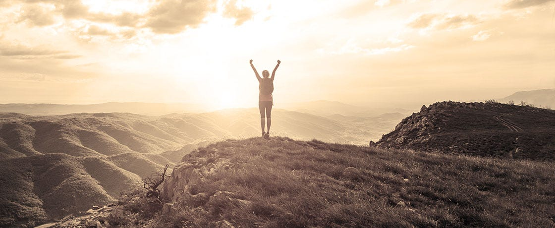 A person standing triumphantly, silhouetted by the sun, having climbed a mountain